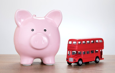 Pink piggy bank alongside a red London bus