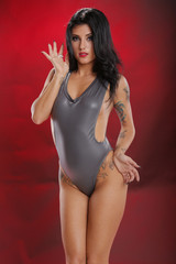 Young woman in silver one piece on red