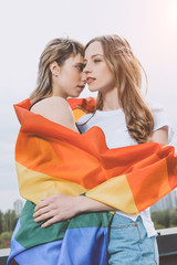 Sensual young lesbian couple posing with lgbt flag outdoors