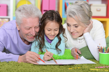 Girl with grandparents drawing picture