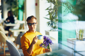 Portrait of trendy romantic guy waiting for date in cafe with bouquet of flowers, drinking coffee