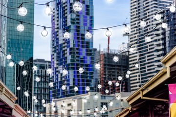 A hanging string of lights at Queen Victoria Markets with the skyline of Melbourne city in the background