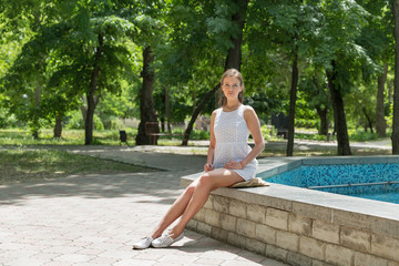 Young beautiful girl in short white dress sit near fountain