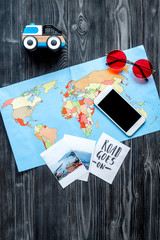 planing trip with child with phone, pictures and map dark background top view space for text