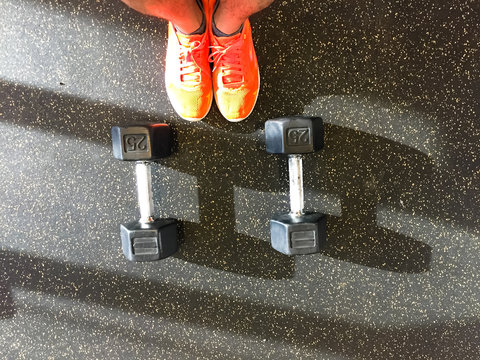 Top view of man feet wear sport shoes and pair of black plastic coated dumbbell in fitness center. Bright sneakers, weights on EPDM (synthetic) rubber background in typical American gym, natural light