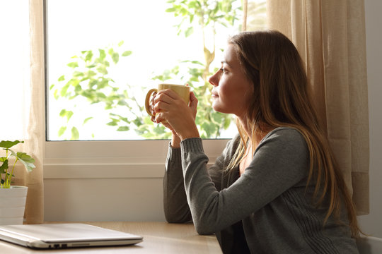 Relaxed woman looking through a window at home