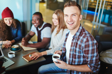Portrait of bearded designer looking at camera with wide smile while having project discussion with colleagues in cozy small cafe