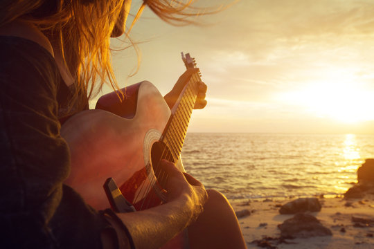 Beautiful young woman playing guitar on sunset beach