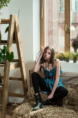 hippie girl sitting on natural hay
