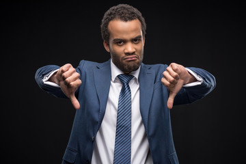 Portrait of upset afro american businessman gesturing thumbs down sign isolated on black