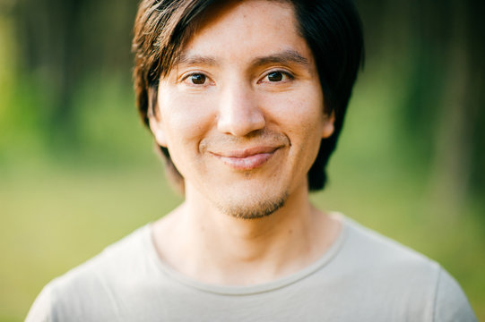 Close up  portrait of native american peruvian indian redskin man with black hair, dark eyes looking at camera with deep reflective and stare eyes. Nature, park, outdoor. Abstract background.