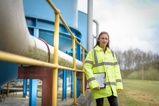 Portrait of female ecologist with waste water plant of car factory
