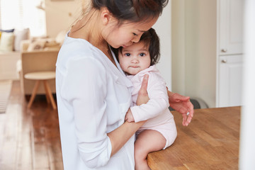 Woman hugging baby daughter on kitchen counter