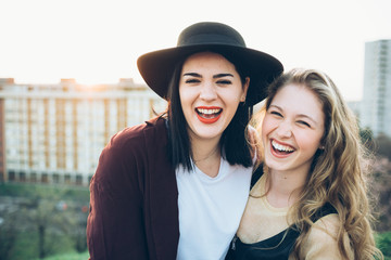 Portrait of two young women, on roof, smiling