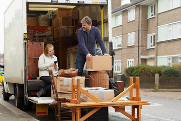 Man and woman loading removal van, woman looking at smartphone