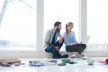 Female and male interior designers looking at laptop in design studio