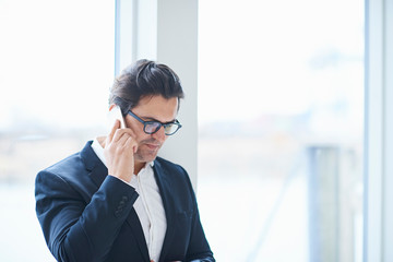 Male designer making smartphone call in design studio window