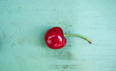 две спелые красные вишни на веточке на голубом деревянном фоне