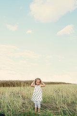 Female toddler standing in wheat field with hand in her hair