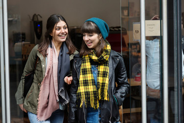 Two young women chatting while leaving cafe