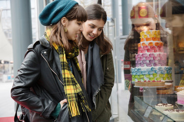 Two young women looking at cake shop window