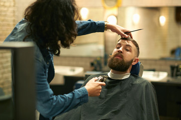 Hairdresser in barbershop trimming customer's beard