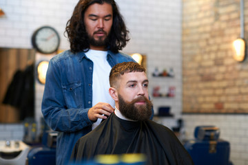 Hairdresser in barbershop putting protective cape on customer