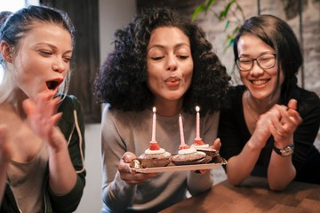 Woman blowing out candles on birthday cakes