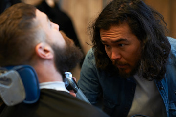 Hairdresser in barbershop trimming customers beard