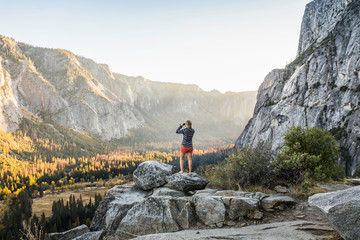Woman on boulder looking out at valley forest through binoculars, Yosemite National Park, California, USA