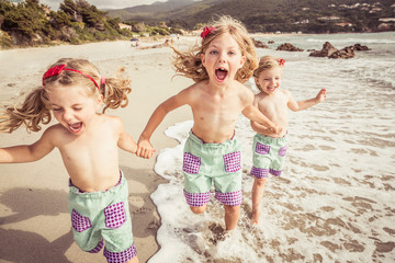 Three young sisters holding hands, running along beach, smiling