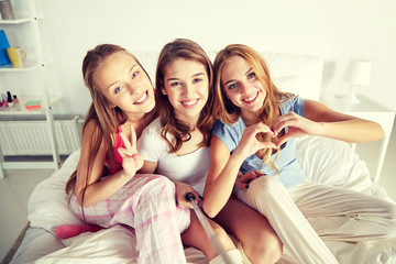 teen girls with selfie stick photographing at home