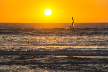 Kitesurfer surfing in the sunset on beach in Cape Town