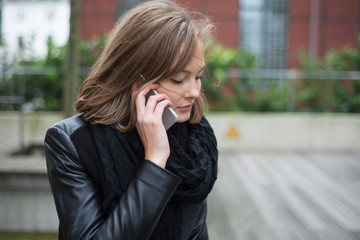 Young businesswoman making smartphone call in city