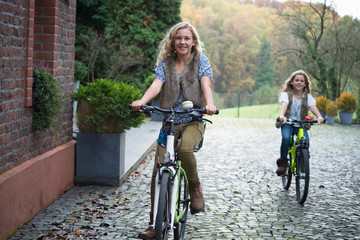 Two sisters cycling together in park