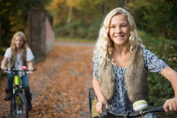 Portrait of two sisters cycling in autumn park