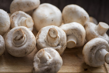 Fresh dirty сhampignon mushroom before peel on the wooden table