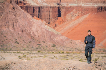 Man in motorcycle gear, standing in front of red sandstone formations in the Salta desert, Salta, Argentina, South America
