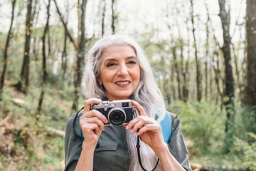 Mature woman with long grey hair photographing in forest, Scandicci, Tuscany, Italy