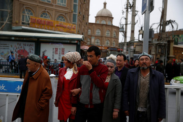 People cross a street in the old town in Kashgar