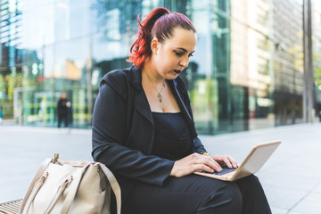Young red haired businesswoman typing on laptop outside office