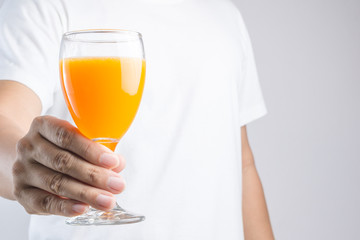 Hand holding glass of orange juice