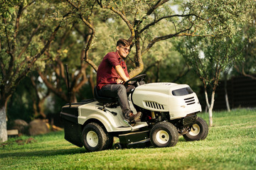 happy handsome worker using ride-on tractor lawn mower