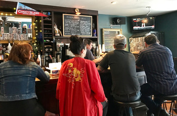 People gather into South 4th Bar to watch former FBI director James Comey testify before the Senate Intelligence committee in Brooklyn