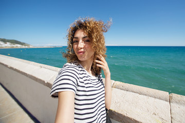 attractive young woman taking selfie outside by the sea