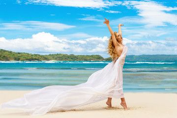 Happy beautiful young girl in fluttering in the wind of white cloth on a tropical beach. Blue sea in the background. Summer vacation concept.