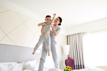happy mother with son in bed at home or hotel room