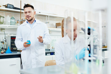 Portrait of two scientists, man and woman, working with test tubes in modern laboratory, performing research