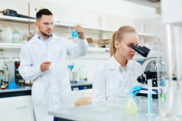 Portrait of two scientists, man and woman, working in modern laboratory, performing bio chemical research