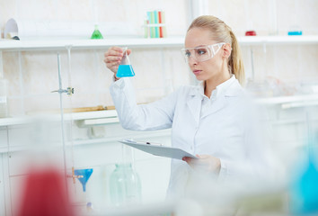 Portrait of beautiful female chemist working on research in modern laboratory holding test tubes